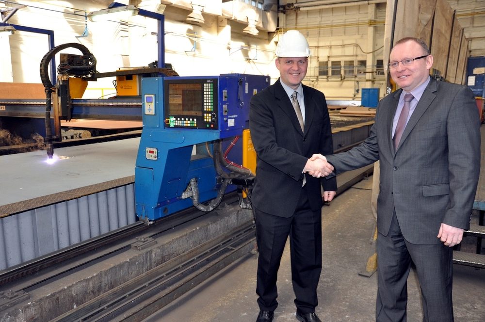 Daniel Riis (on the left) - project manager, BC Ferries and Andrzej Wojtkiewicz, CEO Remontowa Shipbuilding with the steel plates cutting machine in the background. Photo: Grzegorz  Landowski