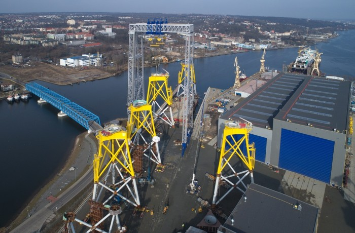 The hulking gantry crane picks the second of three jacket foundations to be loaded onto the awaiting vessel. The fourth (complete) and fifth (unfinished) foundations in the photo will be shipped at a later stage