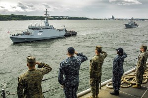 Newly commissioned Polish Navy mine hunter ORP Kormoran, built at Remontowa Shipbuilding, seen passing by USS Oak Hill. U.S. Marines assigned to the 26th Marine Expeditionary Unit (MEU) and Sailors assigned to Amphibious Ready Group 4, salute aboard the Harpers Ferry class dock landing ship USS Oak Hill (LSD 51) during pass in review as part of the celebration of the Polish Navy's 100th birthday, June 24, 2018. Oak Hill, home-ported in Virginia Beach, Virginia, and the 26th MEU are conducting naval operations in the U.S. 6th Fleet area of operations. Photo: Staff Sgt. Dengrier M. Baez / U.S. Marine Corps